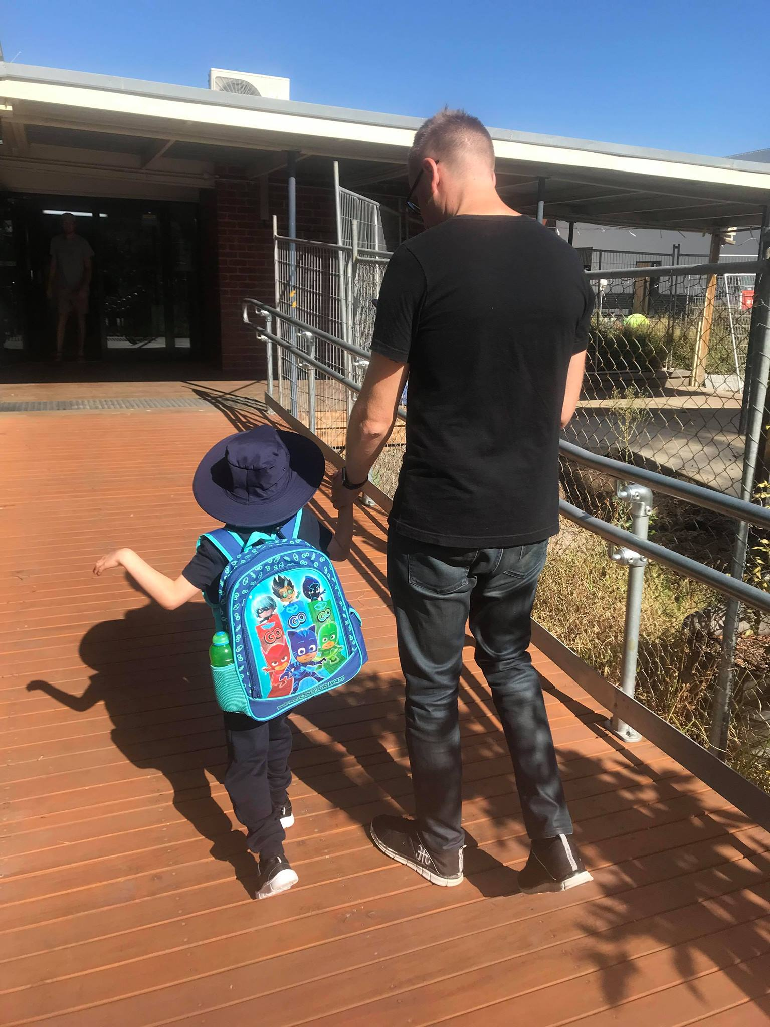 Luca holds his father's hand while he walks to his first day of school.