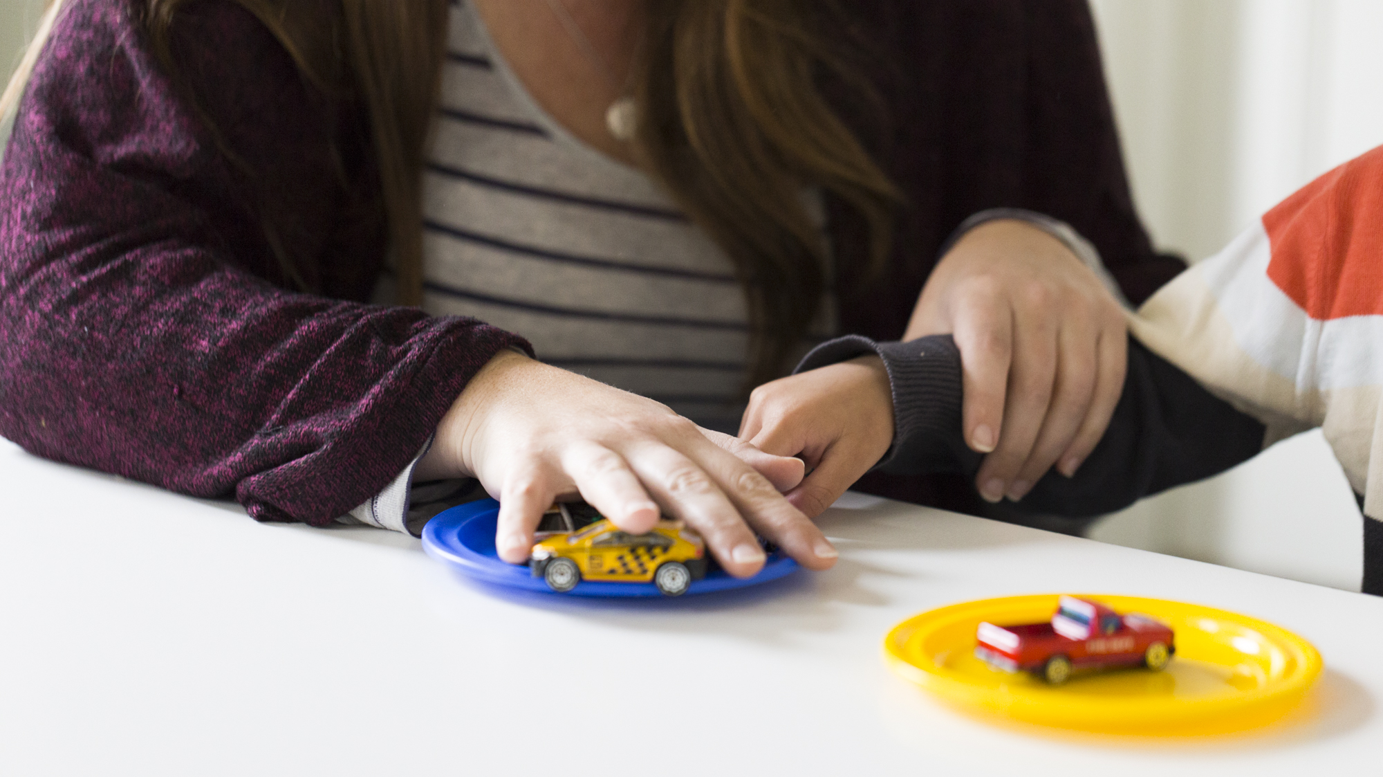 Therapist learning to provide ABA therapy to a child with autism using racing car toys