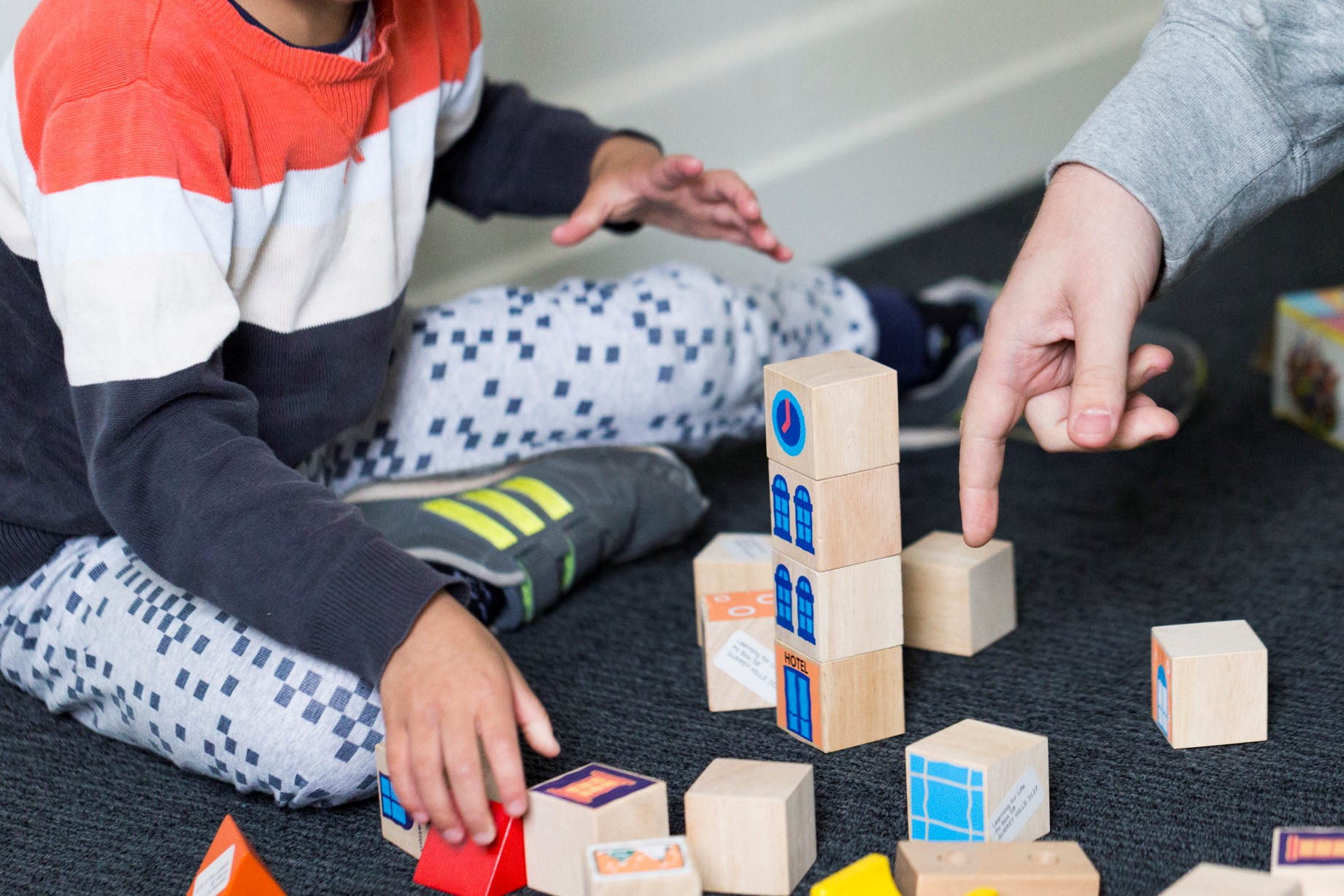 ABA therapist working with autistic child using building blocks